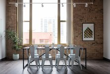 Large table in a room in front of a large window with building outside the window, photo by Breather, @Breather